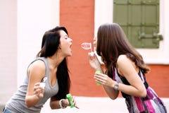 Подруги с пузырями мыла outdoors Стоковые Изображения RF