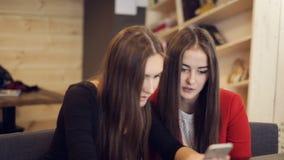 2 подруги с смехом smartphone в кафе акции видеоматериалы