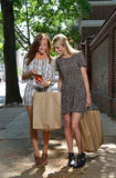 Подруги ходя по магазинам в городе - смотреть сотовый телефон Стоковое Фото