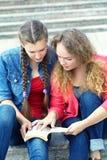 2 подруги читая книгу Стоковые Изображения RF