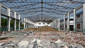 Подрывание старого здания фабрики сигналя внутри при экскаватор работая в дальнем конце акции видеоматериалы
