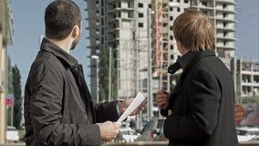 Подрядчик и инвестор обсуждая проект жилищного строительства видеоматериал