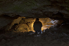 Подсвеченный человек исследуя темную пещеру Стоковое Изображение RF