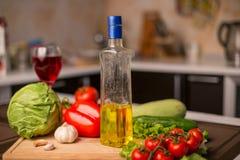 Подсолнечное масло на таблице около свежих овощей Стоковое Фото