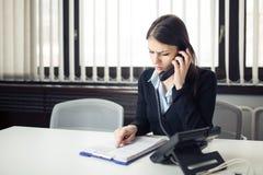 Получать телефонный звонок плохой новости Смотреть смущенный проверяющ примечания и обработку документов Менеджер разрешая ошибку стоковое фото