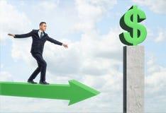 Получают, что зеленеет бизнесмен идя на стрелку и большой знак доллара Стоковая Фотография RF