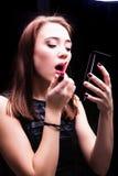 получающ идя губную помаду смотря состав отразьте партию ночи кладя готовый красный цвет к женщине стоковое фото