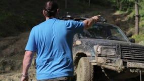 Полученное SUV вставило в грязи и пробовать пойти вне через ворот в лесе видеоматериал