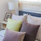 Подушки Брайна и зеленые подушки на кровати в спальне Стоковое фото RF