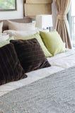 Подушки Брайна и зеленые подушки на кровати в спальне Стоковые Фотографии RF
