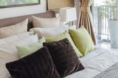 Подушки Брайна и зеленые подушки на кровати в спальне Стоковые Изображения