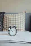 Подушки картины будильника и графика на кровати Стоковые Изображения