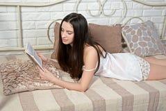 Полу-нагая красивая девушка на кровати читая книгу Стоковые Изображения RF
