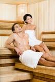Полу-нагой человек и молодая женщина ослабляя в сауне Стоковые Фото