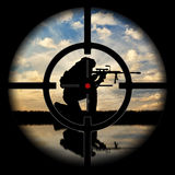 Под дулом пистолета силуэт террориста против захода солнца Стоковая Фотография RF