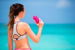 Подходящая активная вода питья молодой женщины на белом пляже Стоковые Изображения