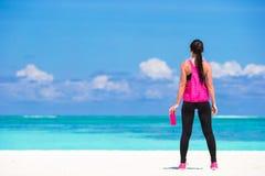Подходящая вода питья молодой женщины на белом пляже Стоковые Изображения