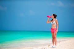 Подходящая вода питья молодой женщины на белом пляже Стоковые Фотографии RF