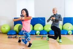 Подходящая женская спортсменка делая тренировку выпада реверанса с гантелями в классе студии фитнеса группы стоковое фото rf