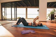Подходящая женщина лежа на циновке тренировки с мобильным телефоном Стоковые Изображения RF
