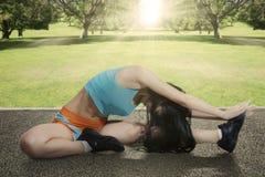 Подходящая женщина делая разминку на парке Стоковые Фотографии RF