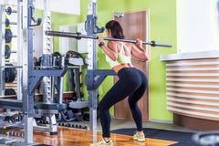 Подходящая женщина делая сидение на корточках с штангой в спортзале Стоковые Изображения