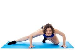 Подходящая женщина заискивая на голубой циновке, съемке студии Стоковое фото RF
