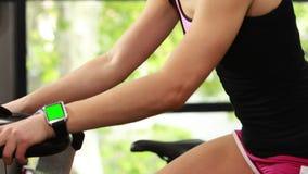 Подходящая женщина используя велотренажер и умный вахту сток-видео