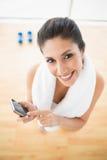 Подходящая женщина используя smartphone принимая пролом от разминки усмехаясь на камере Стоковые Изображения