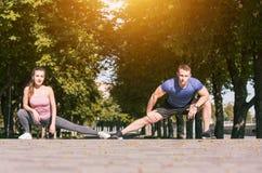 Подходящая женщина и человек фитнеса делая протягивающ тренировки outdoors на парке Стоковые Фотографии RF