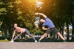 Подходящая женщина и человек фитнеса делая протягивающ тренировки outdoors на парке Стоковая Фотография