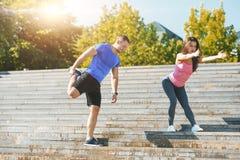 Подходящая женщина и человек фитнеса делая протягивающ тренировки outdoors на парке Стоковая Фотография RF