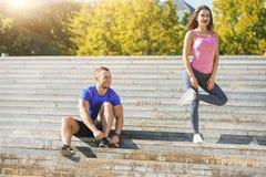 Подходящая женщина и человек фитнеса делая протягивающ тренировки outdoors на парке Стоковое Изображение RF