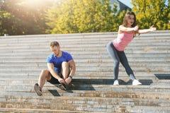 Подходящая женщина и человек фитнеса делая протягивающ тренировки outdoors на парке Стоковое фото RF