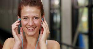 Подходящая женщина кладя наушники для того чтобы слушать к музыке видеоматериал