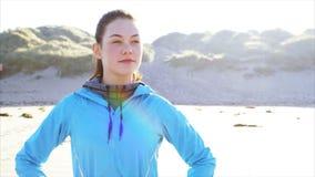 Подходящая женщина наслаждаясь свежим воздухом на пляже после бега сток-видео