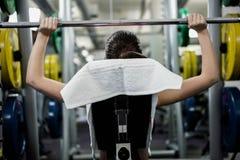 Подходящая женщина поднимая жим лёжа штанги стоковая фотография rf
