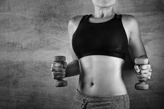 Подходящая женщина работая с весами на предпосылке бетонной стены в спортзале Отсутствие стороны, здоровой концепции образа жизни Стоковые Изображения