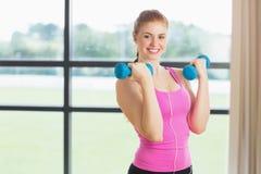 Подходящая женщина работая с гантелями в студии фитнеса Стоковые Изображения RF