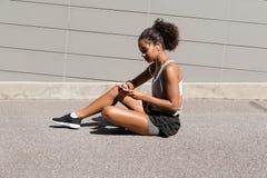 Подходящая женщина сидя на дороге Стоковые Изображения