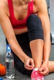 Подходящая женщина сидя на шнурке пола и связи Стоковые Фотографии RF