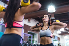 Подходящая женщина смотря зеркало, работая с kettlebell в спортзале Стоковые Изображения RF
