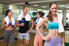 Подходящая женщина усмехаясь на камере в занятой студии фитнеса Стоковое фото RF