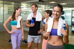Подходящая женщина усмехаясь на камере в занятой студии фитнеса Стоковое Изображение