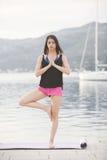 Подходящая здоровая женщина протягивая на циновке йоги на взморье пляжа, делая хрусты тренировки подбрюшные, тренировку и образ ж стоковое изображение rf