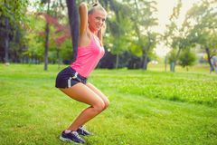 Подходящая и мышечная женщина в парке, делающ сидения на корточках и ход Стоковое фото RF