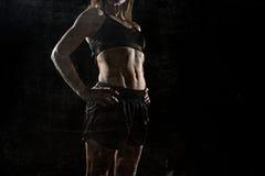 Подходящая и сильная женщина спорта держа представлять вызывающий в холодной ориентации с рантом построила тело Стоковые Фотографии RF