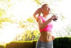 Подходящая молодая женщина бежать outdoors Стоковая Фотография