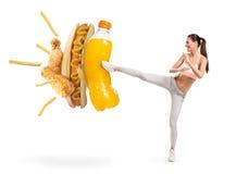 Подходящая молодая женщина воюя соду и высококалорийную вредную пищу стоковые фото