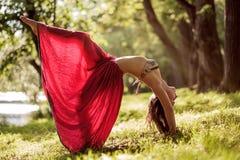 Подходящая молодая красивая женщина нося красную юбку разрабатывая outdoors в парке на летний день, делая представление моста от  Стоковая Фотография